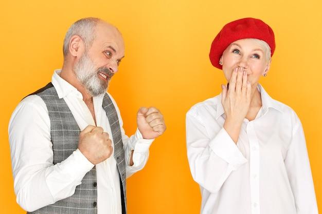 口をあえぎ、怒ったひげを生やした男が拳を握りしめ、怒り狂った表情をして、妻を殴りに行く赤いベレー帽をかぶった軽薄な屈託のない中年女性のスタジオショット。家庭内暴力 無料写真