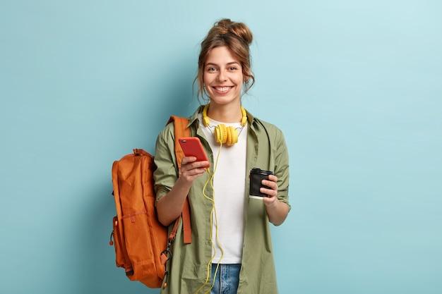 Студийный снимок радостной студентки, которая после лекций отдыхает на кофе, слушает аудиокнигу в наушниках, наслаждается записью с веб-сайта, использует мобильный телефон для общения в чате, носит рюкзак на спине. Бесплатные Фотографии