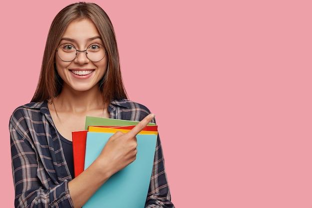 Студийный снимок красивой молодой деловой женщины, позирующей на розовой стене в очках Бесплатные Фотографии