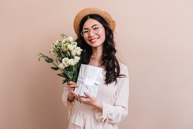 白い花を持つ日本人女性のスタジオショット。トルコギキョウの花束とギフトを保持している魅力的なアジアのモデル。 無料写真