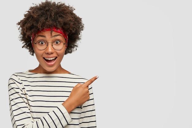 ポジティブなダークスキンの女の子のスタジオショットは、丸い透明なメガネをかけています 無料写真