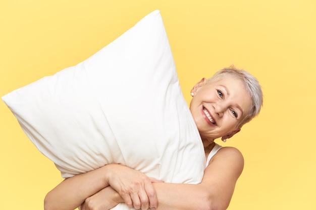 흰 깃털 베개를 껴안은 긍정적 인 졸린 성숙한 유럽 여성의 스튜디오 샷, 긴 하루 후 피곤한 잠자리에 들기. 무료 사진