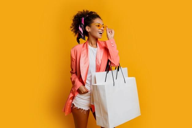 노란색 배경 위에 흰색 쇼핑백 서와 함께 예쁜 흑인 여자의 스튜디오 샷. 유행 봄 유행 모양. 무료 사진
