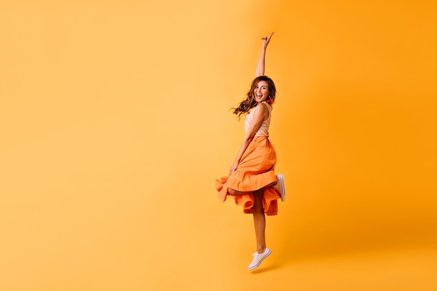 オレンジ色のスカートと白い靴のかわいい女の子のスタジオショット。黄色にジャンプする興奮した赤毛の女性。 無料写真