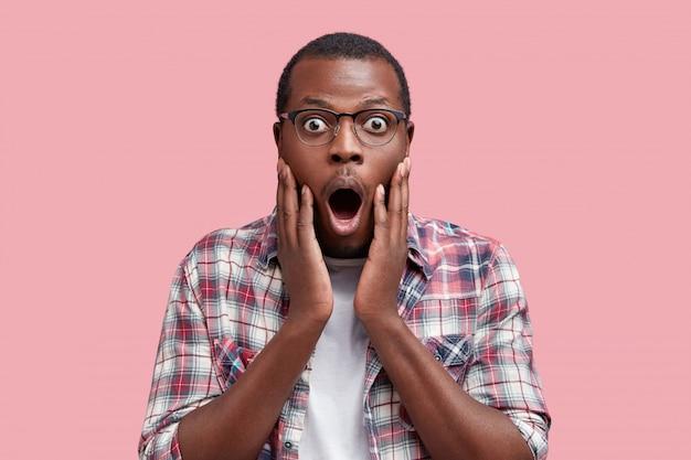 Студийный снимок испуганного, испуганного темнокожего африканского покупателя, шокированного ценами в магазине, которому не хватает денег, чтобы что-то купить, изолированное на розовом Бесплатные Фотографии