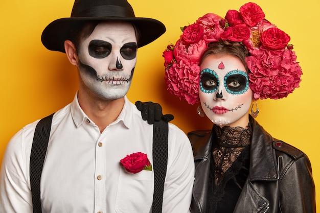 真面目なカップルのスタジオショットは、鮮やかな化粧をして、伝統的なメキシコの休日を祝い、花で作られた花輪を着て、黄色の背景の上に隔離された衣装パーティーに来ます。死の日の概念 無料写真