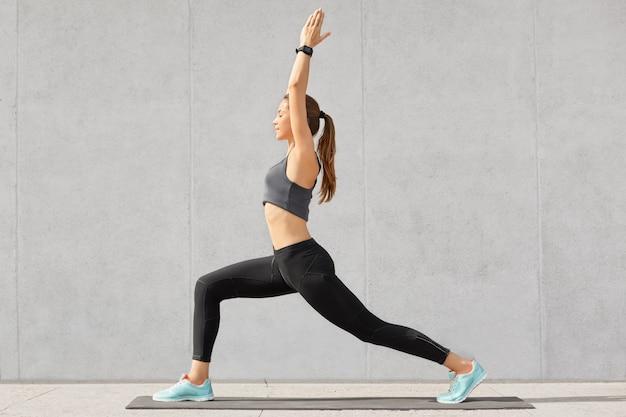 슬림 여자의 스튜디오 샷 손을 박수, 팔 밸런스 운동을 수행, 다락방 인테리어에서 운동, 다이어트를 유지, 건강한 라이프 스타일을 가지고 무료 사진