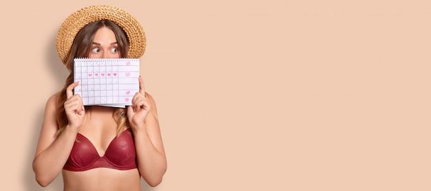 Студийный снимок ошеломленной европейской женщины держит календарь периода, лицо минуса, одетое в купальник, удивленное выражение лица, стоит на бежевом с копией пространства для вашей рекламы Premium Фотографии