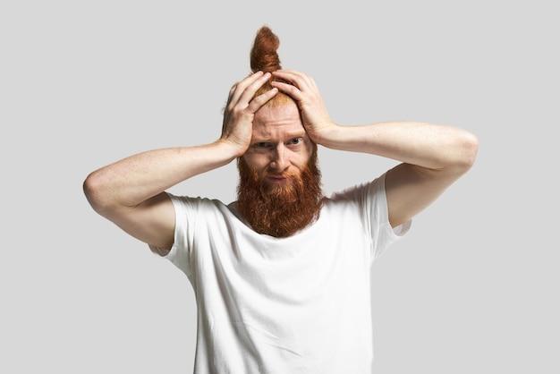 Студийный снимок стильного молодого хипстера в белой футболке, держащего руки за голову, с паническим отчаянием на лице после того, как он узнал ужасные новости. разочарованный бородатый парень сталкивается со стрессом Бесплатные Фотографии