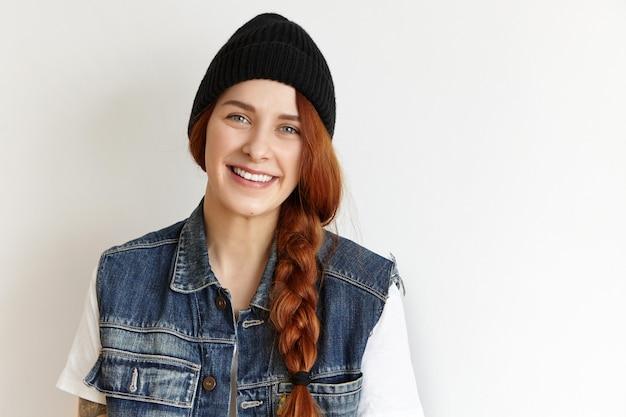 Студийный снимок стильной молодой рыжей женщины в джинсовой куртке без рукавов поверх белой футболки Бесплатные Фотографии