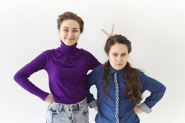 白い壁の背景に対してポーズをとっている2人のブルネットの姉妹のスタジオショット:ジェスチャーを作って広く笑っている年配の女の子 無料写真