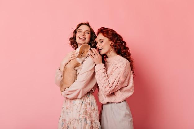 강아지와 두 친구의 스튜디오 샷입니다. 분홍색 배경에 강아지와 함께 연주 곱슬 소녀. 무료 사진