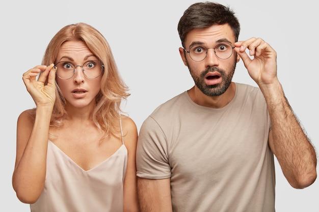 Студийный снимок, на котором двое удивленных потрясающих мужчин и женщин смотрят в недоумении, трогают оправу очков, пораженные внезапной новостью Бесплатные Фотографии
