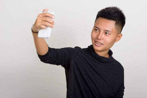 흰색 배경에 짧은 머리를 가진 젊은 아시아 레즈비언 여자의 스튜디오 샷 프리미엄 사진