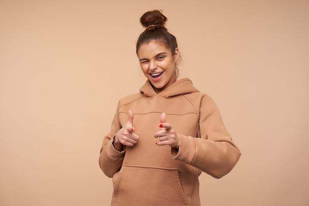 베이지 색 벽 위에 절연 제기 손으로 앞에 보여주는 동안 행복하게 윙크하는 롤빵 헤어 스타일을 가진 젊은 매력적인 갈색 머리 여자의 스튜디오 샷 무료 사진