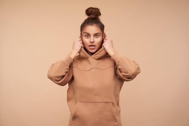 베이지 색 벽 위에 서있는 동안 조심스럽게 정면을 보면서 그녀의 후드에 손을 잡고 자연 화장과 젊은 갈색 머리 여자의 스튜디오 샷 무료 사진