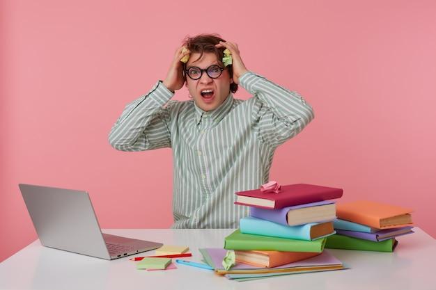 眼鏡をかけた若い狂気の男のスタジオショット、空白のシャツを着て、本を持ってテーブルに座って、ラップトップで働いて、怒って不満に見えます、何かがおかしいです。ピンクの背景に分離。 無料写真