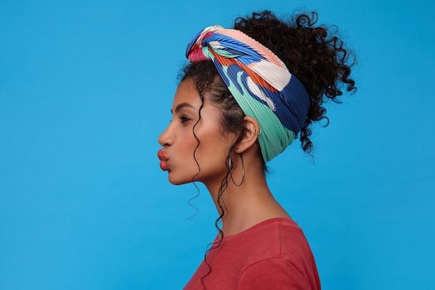 青い壁の上に立って、前方を見ながらエアキスで唇を折りたたむマルチカラーのヘッドバンドを持つ若い黒髪の巻き毛の女性のスタジオショット 無料写真