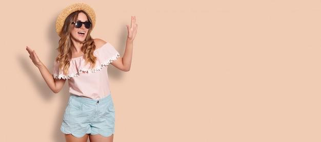 Студия выстрел молодой женщины в модной одежде, любит летнее время, позирует на бежевом с копией пространства для вашей рекламы или рекламного контента. концепция образа жизни Premium Фотографии