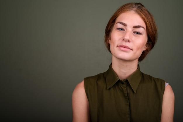 色付きの背景に緑のノースリーブトップを着ている若い女性のスタジオ撮影 Premium写真