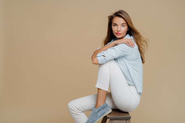 Studio shot of restful beautiful caucasian woman sits on chair, wears shirt, white trousers and shoes Premium Photo