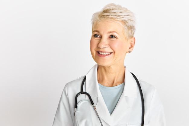 Studio shot di successo bionda di mezza età terapista femminile in posa isolata con un ampio sorriso felice che indossa l'abito medico bianco e lo stetoscopio intorno al collo Foto Gratuite