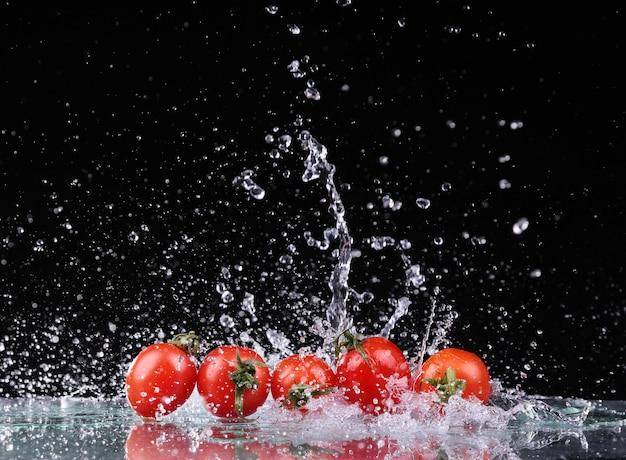 Studio shot with freeze motion of cherry tomatoes in water splash on black background Premium Photo