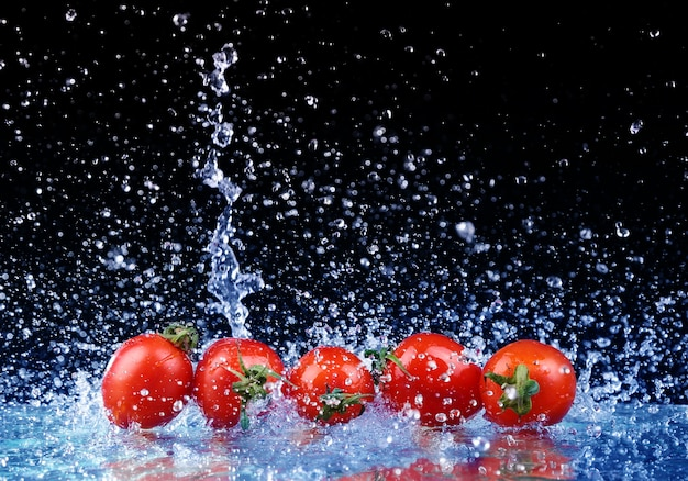 Studio shot with freeze motion of cherry tomatoes in water splash on black background Premium Photo