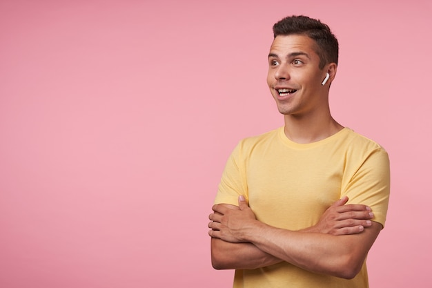 Studio shot del giovane maschio bruna con le cuffie guardando emotivamente avanti con un ampio sorriso e tenendo le mani giunte sul petto, isolato su sfondo rosa Foto Gratuite
