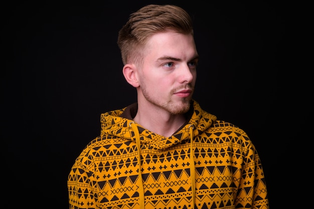 Studio shot of young handsome man against black background Premium Photo