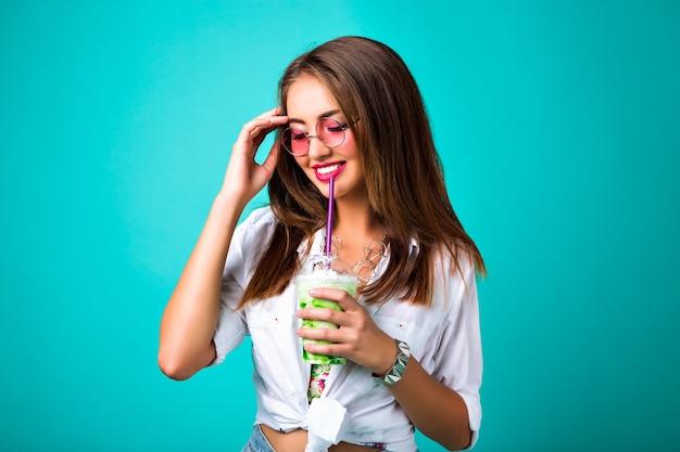 Фото моды весны студии улыбающейся девушки, ретро-стиля хиппи, питья вкусного мятного фона смузи, счастливой веселой хипстерской девушки наслаждается своим коктейлем, позитивным настроением. Бесплатные Фотографии