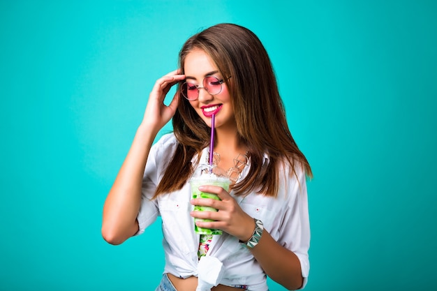 Studio spring fashion photo of smiling girl, hippie retro style, drinking tasty smoothie  mint background, happy cheerful hipster girl enjoy her cocktail, positive mood. Free Photo