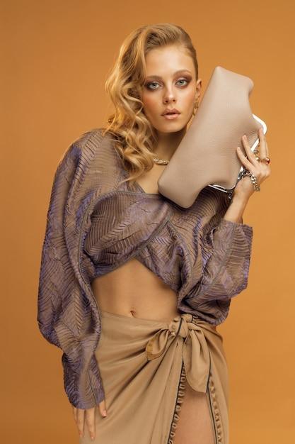 스튜디오 세로 사진, 유행의 옷을 입은 여성 모델과 그녀의 손에 세련된 가방, 베이지 색 단색 배경. 고품질 사진 프리미엄 사진