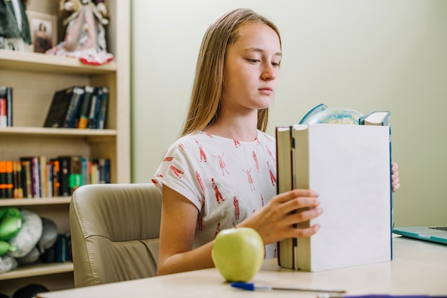 Studying girl with stacked books Free Photo