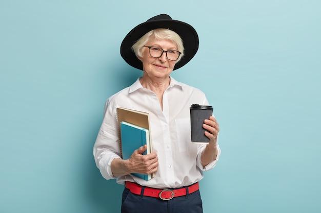 老後の勉強。黒い帽子をかぶったしわの寄った女性を喜ばせ、2つのメモ帳、持ち帰り用のコーヒーを持ち、青い壁に隔離された講義を行う準備をします。人、年金、飲酒の概念 無料写真
