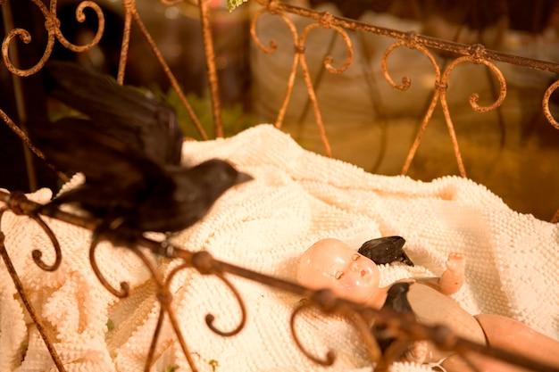 Stuffed blackbird and baby doll in antique crib Premium Photo