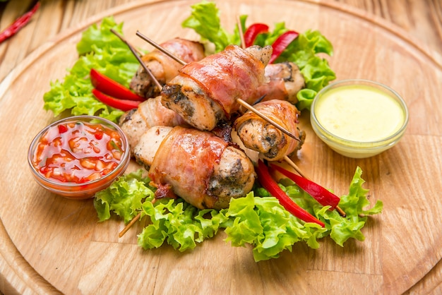 Stuffed chicken breast wrapped in bacon on a plate close-up. horizontal Premium Photo