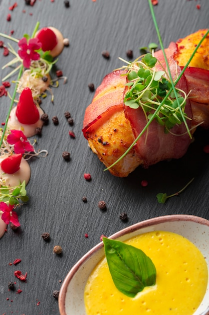 Stuffed chicken breast wrapped in bacon on a plate close-up Premium Photo