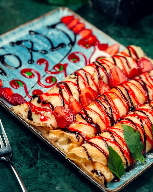 Stuffed crepe garnished with strawberry and chocolate syrups Free Photo
