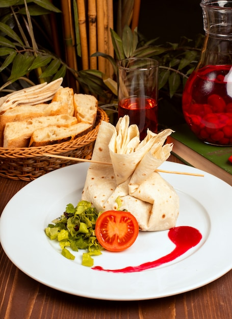 Stuffed filled lavash with tomato and vegetables in white plate Free Photo