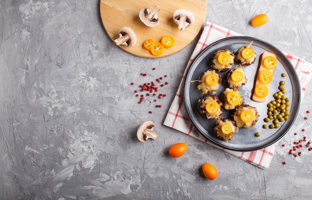 Stuffed fried champignons with cheese, kumquats and green peas on a gray concrete background Premium Photo
