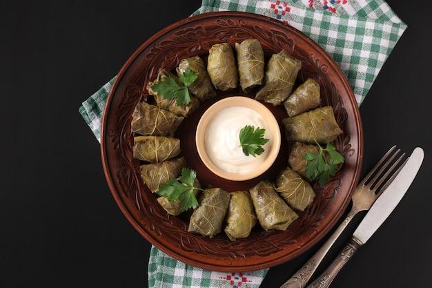 Фаршированные виноградные листья - традиционная средиземноморская кухня, долма на коричневой тарелке со свежей петрушкой и чесночным соусом на черном фоне, крупным планом, вид сверху Premium Фотографии