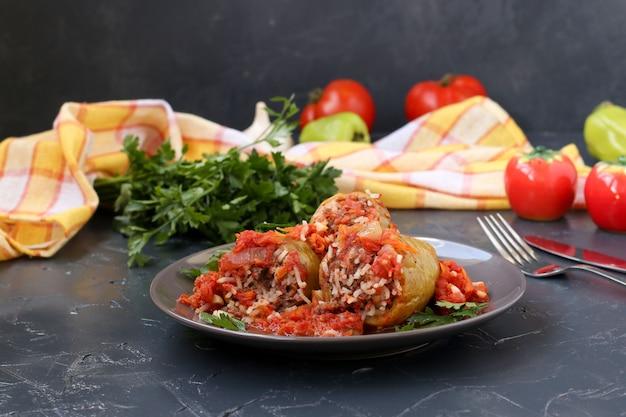 暗闇の中でプレートにある肉、米、トマトソースのピーマンの詰め物 Premium写真