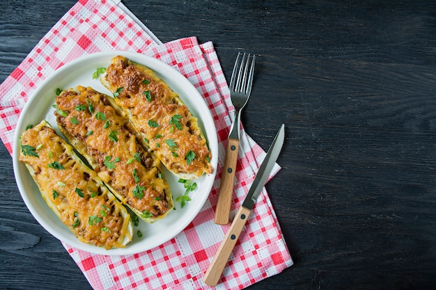 Stuffed zucchini with minced meat and grated cheese Premium Photo