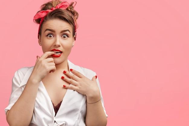 Ошеломленная красивая женщина нервно кусает палец, смотрит с удивленным выражением лица, получает неожиданный реквизит, позирует Бесплатные Фотографии