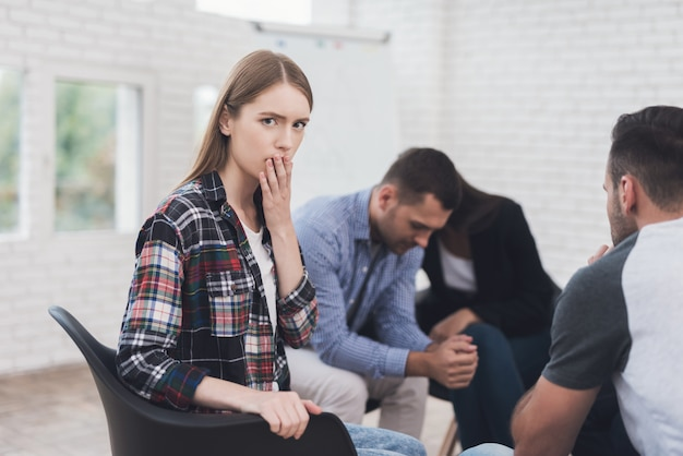Stunned girl is sitting in group therapy session. Premium Photo