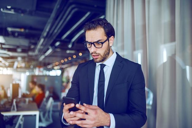 見事なハンサムな白人のひげを生やした実業家のスーツと眼鏡が会社に立って不快なメッセージを読んで。私 Premium写真