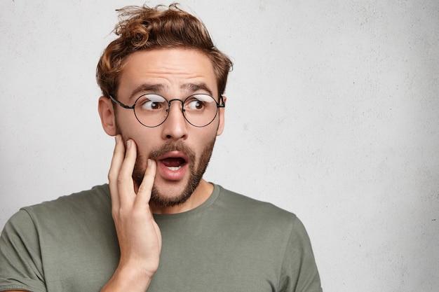 あごを落とした驚いたショックを受けたあごひげを生やした男は、信じられないほどの話を聞いています、 無料写真