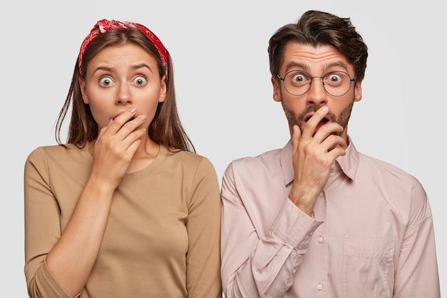Ошеломленная молодая пара позирует у белой стены Бесплатные Фотографии
