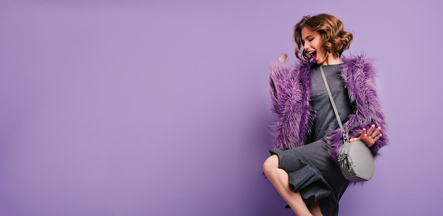 Stunning barefooted woman in trendy fur coat dancing and laughing on photoshoot Free Photo